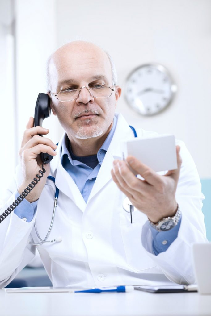 Doctor on the phone with a patient holding a small box