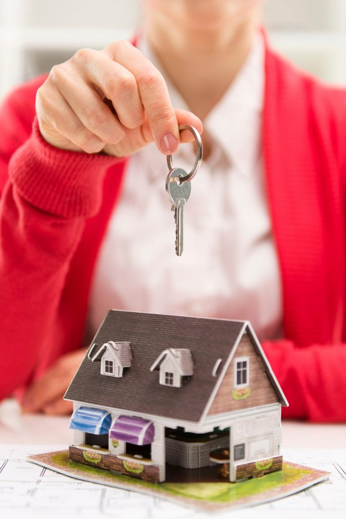 Person holding a key above a small model house