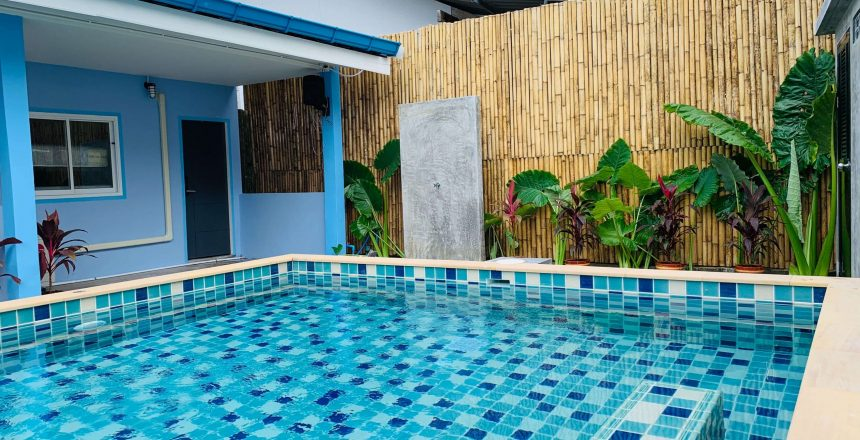 beautiful pool in backyard of house with bamboo fencing